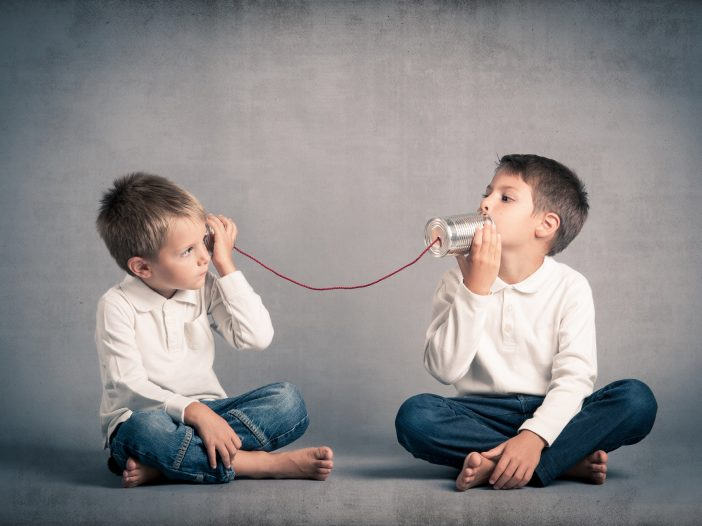 Young brothers talking with tin can telephone on grunge backgrou