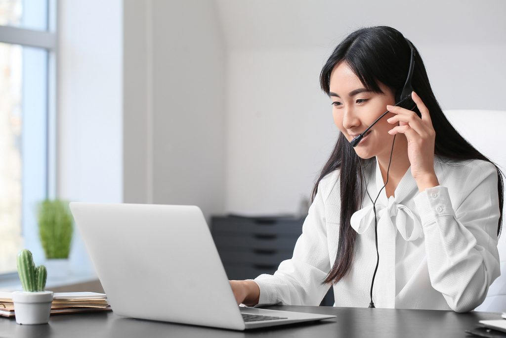female in office using her internet phone service and headset
